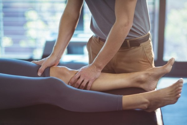 Physiotherapist massaging knee