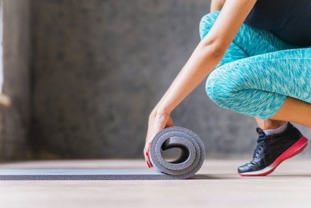 Woman rolling out exercise Mat
