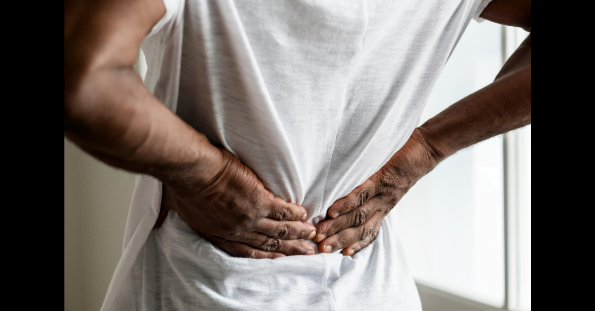 Man holding back due to middle back pain