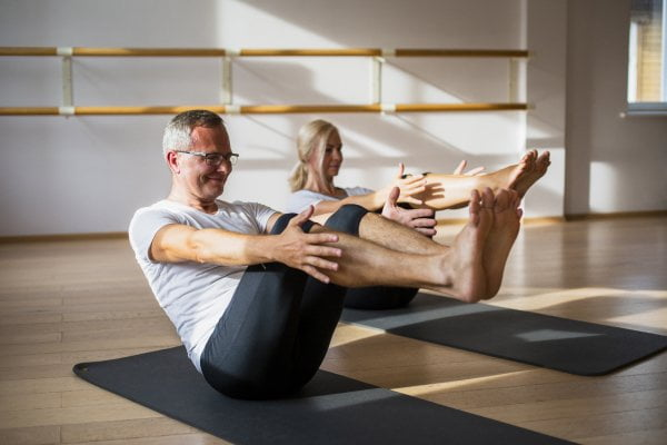 Old Man and Woman practicing yoga together