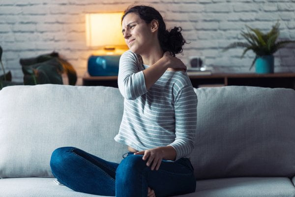 Woman sitting on a sofa with back pain